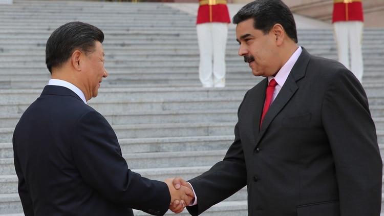 Xi Jinping saluda al dictador Nicolás Maduro durante una cumbre que tuvieron en septiembre de 2018 en Beijing. El caso venezolano es un claro ejemplo de cómo el régimen chino aprovechó la debilidad institucional del país para hacer negocios (AFP)