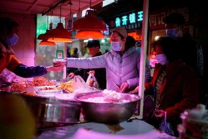 Varias personas con mascarilla esperan para comprar comida en un puesto callejero de Wuhan, en la provincia de Hubei, China, el 8 de febrero de 2021. REUTERS/Aly Song