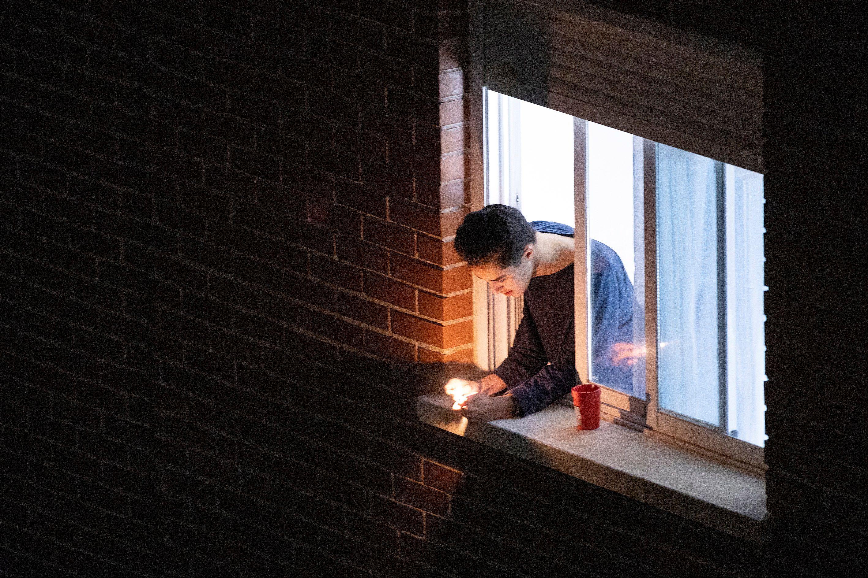 Un joven mira su móvil asomado a la ventana de su habitación durante el confinamiento. EFE/Domenech Castelló/Archivo