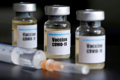 """FOTO DE ARCHIVO: Pequeños fracos médicos con etiquetas en las que se puede leer """"Vacuna COVID-19"""" en inglés junto a una jeringuilla en esta fotografía de ilustración tomada el 10 de abril de 2020. REUTERS/Dado Ruvic/Ilustración"""