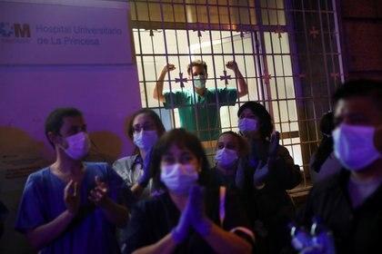 Los trabajadores médicos aplauden para rendir homenaje a todos los profesionales de la salud que están lidiando con el brote de COVID-19, en el hospital La Princesa de Madrid, España, el 25 de marzo de 2020. (REUTERS/Susana Vera)