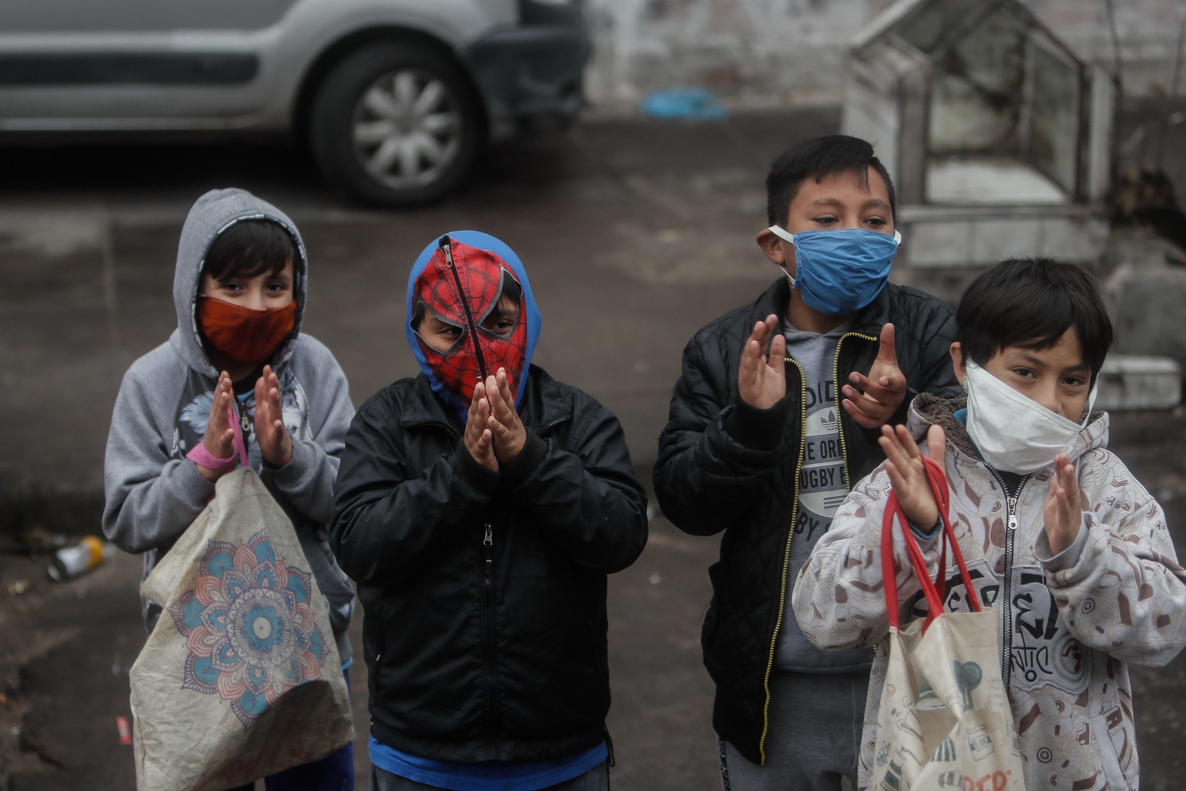 Un grupo de niños aplaude afuera de a un comedor comunitario durante la crisis del coronavirus en el barrio Padre Rodolfo Ricciardelli, anteriormente conocido como Villa 1-11-14, en la Ciudad de Buenos Aires (Argentina). EFE/Juan Ignacio Roncoroni/Archivo