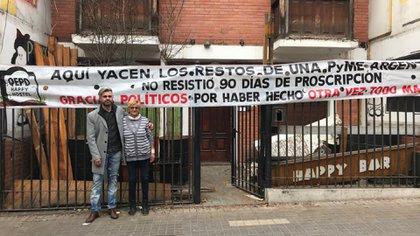 """Gabriel González frente al hostel que tuvo que cerrar y al cartel que colgó: """"QEPD Happy Hostel"""""""