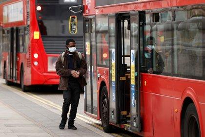Un hombre con máscara facil se sube al autobús en Londres REUTERS/John Sibley