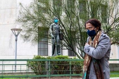 07/05/2020 Una mujer pasa frente a una estatua con mascarilla en Montevideo, acción promovida por el Gobierno para fomentar el uso de mascarilla. POLITICA MAURICIO ZINA / ZUMA PRESS / CONTACTOPHOTO