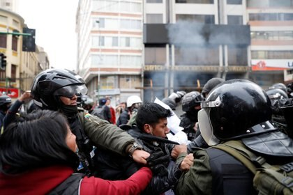 A demonstrator scuffles with members of the security forces during clashes between supporters of former Bolivian President Evo Morales and security forces, in La Paz, Bolivia November 13, 2019. REUTERS/Carlos Garcia Rawlins