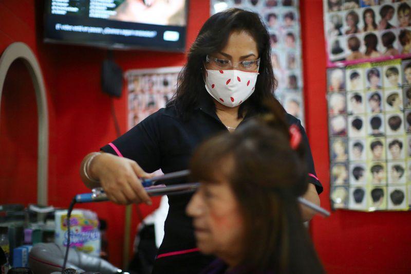 """FOTO DE ARCHIVO: Una estilista con mascarilla peina el cabello de una mujer en el salón de belleza """"Imagen"""", en la Ciudad de México, México. 22 de septiembre de 2020. REUTERS/Edgard Garrido"""