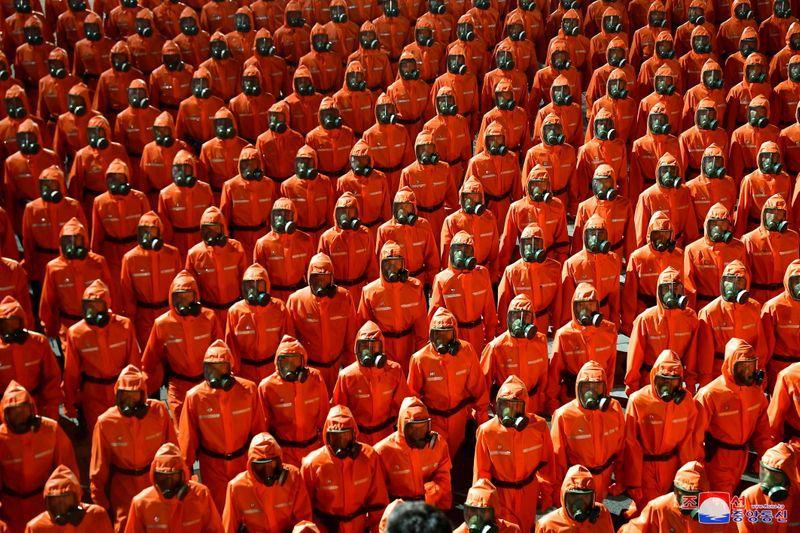 Personas vestidas con trajes naranjas contra materiales peligrosos desfilan durante el desfile militar celebrado con motivo del 73 aniversario de la fundación de Corea del Norte en la Plaza Kim Il Sung de Pyongyang, el 9 de septiembre de 2021. KCNA vía Reuters.