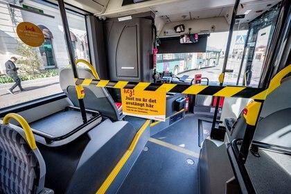 Un letrero dentro de un autobús indica a los pasajeros subir por la entrada trasera para proteger a los conductores del coronavirus, en Malmö, Suecia, el 17 de abril de 2020. (Johan Nilsson/ Agencia de Noticias TT/vía REUTERS)
