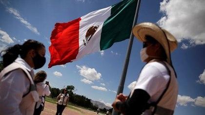Imagen de archivo. Empleados del gobierno mexicano se paran junto a una bandera nacional a media asta durante un duelo nacional de 30 días por las muertes e infecciones causadas por la enfermedad del coronavirus (COVID-19), en Ciudad Juárez, México.1 de septiembre de 2020. REUTERS / Jose Luis González