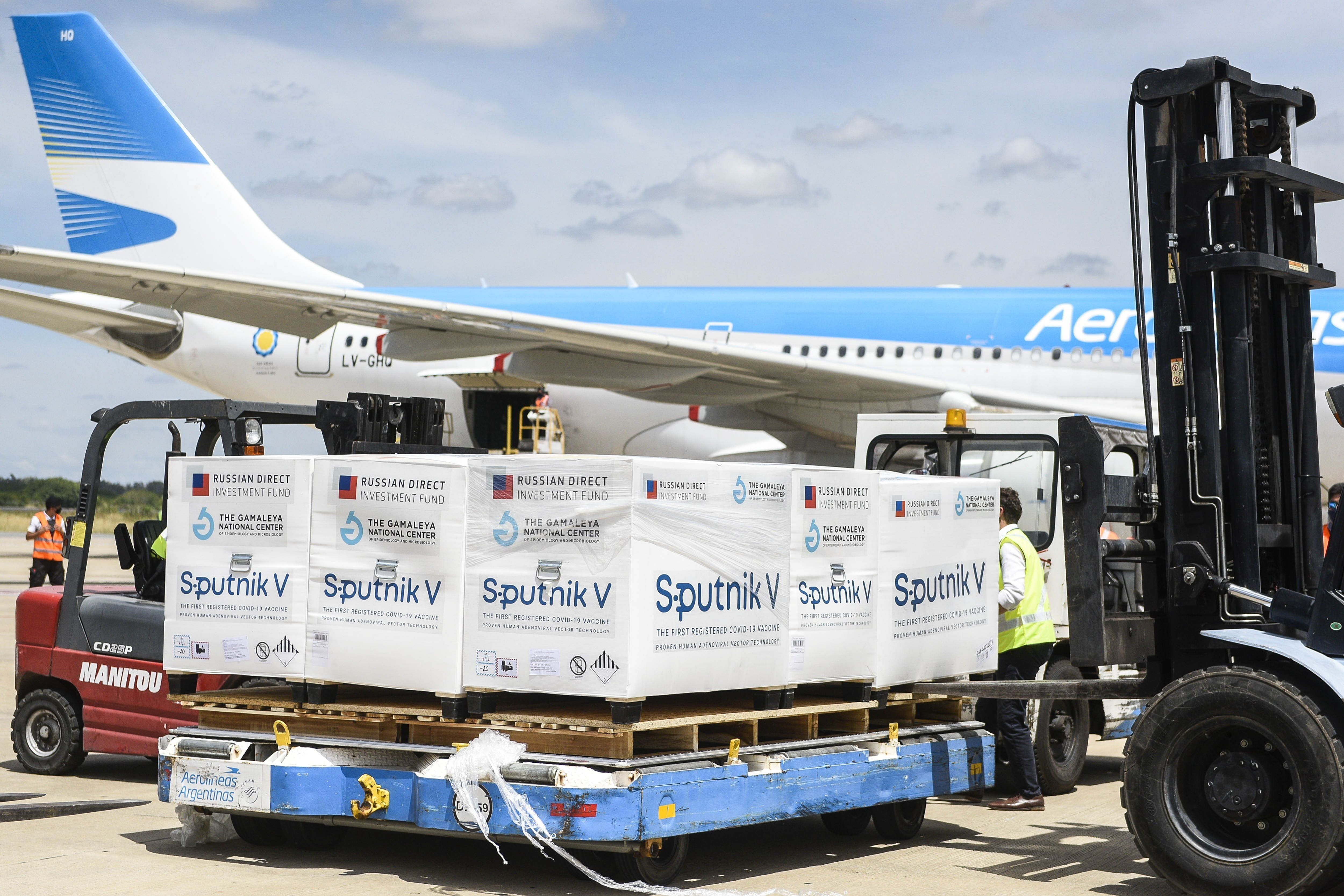 Fotografía cedida por la Presidencia de Argentina que muestra el cargamento de vacunas Sputnik-V que el avión (atrás) de la estatal Aerolíneas Argentinas transportó el 16 de enero de 2021. EFE/Presidencia de Argentina
