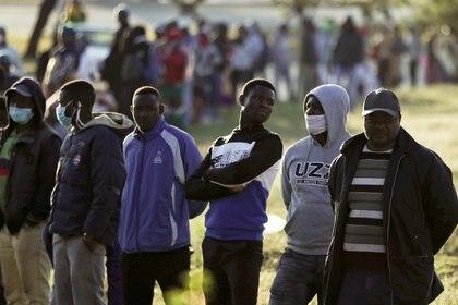 Comerciantes informales hacen cola mientras esperan para solicitar un permiso en medio de un cierre nacional destinado a limitar la propagación del coronavirus en Soweto (Sudáfrica) el 23 de abril de 2020. REUTERS/Siphiwe Sibeko