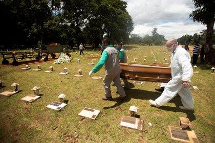 Trabajadores cargan un féretro con una víctima mortal de covid-19 rumbo a su entierro, el 11 de marzo del 2021, en el cementerio Campo da Esperança, en Brasilia (Brasil). EFE/ Joédson Alves