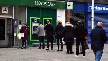 Una fila manteniendo la distancia social para obtener dinero en un cajero automático de Barrow-in-Furness, al noroeste de Inglaterra.