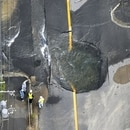 Water flows out from cracks in a road damaged by an earthquake in Takatsuki, Osaka prefecture, western Japan, in this photo taken by Kyodo June 18, 2018. Mandatory credit Kyodo/via REUTERS ATTENTION EDITORS - THIS IMAGE WAS PROVIDED BY A THIRD PARTY. MANDATORY CREDIT. JAPAN OUT. NO COMMERCIAL OR EDITORIAL SALES IN JAPAN. TPX IMAGES OF THE DAY