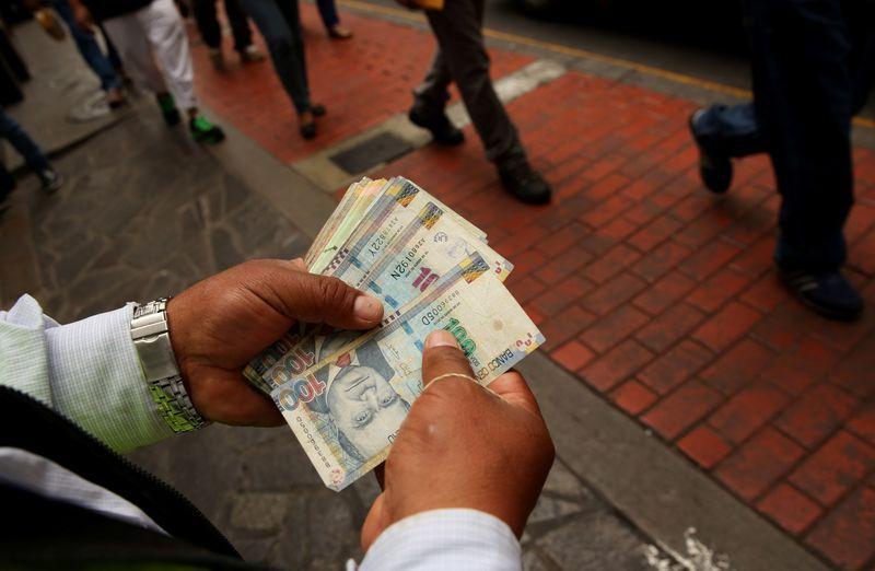 Un cambista de dinero sostiene billetes de sol peruano en una calle del centro de Lima. El dólar se disparó ante la incertidumbre política. La pandemia golpeó duramente a la economía peruana. REUTERS / Mariana Bazo