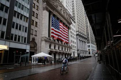 Un hombre conduciendo una bicicleta frente a la Bolsa de Valores de Nueva York (NYSE), en medio del brote de la enfermedad causada por el coronavirus (REUTERS/Mike Segar)