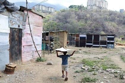 Foto de archivo ilustrativa de un niño llevando una lámina de hojalata cerca de un grupo de casas hechas con barro, palos y hojalata levantadas en un terreno baldío en el que las familias se establecen porque no pueden pagar un alquiler, en el municipio de Sucre, cerca de Caracas.  Jun 12, 2020. REUTERS/Manaure Quintero