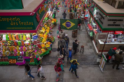 People wearing protective masks walk through a market in Sao Paulo, Brazil, on Thursday, July 30, 2020. Brazil added 69,074 cases on Wednesday, pushing the total number of infections to over 2.55 million, according to the Health Ministry. Photographer: Jonne Roriz/Bloomberg