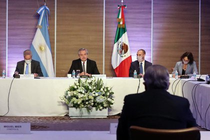 """Handout picture released by the Argentine Presidency showing Argentina's President Alberto Fernandez (C), accompanied by (L-R) his Foreign Minister Felipe Sola, Economy Minister Martin Guzman and deputy Chief Cabinet Cecilia Todesca, during a meeting with Mexican businessmen with investments in Argentina, in Mexico City on February 22, 2021. - Argentina's President Alberto Fernandez will meet his counterpart Andres Manuel Lopez Obrador and visit the Liomont laboratory, where the COVID-19 vaccine developed by the Anglo-Swedish firm AstraZeneca is packaged. (Photo by Esteban COLLAZO / Argentinian Presidency / AFP) / RESTRICTED TO EDITORIAL USE - MANDATORY CREDIT """"AFP PHOTO / ARGENTINA'S PRESIDENCY / ESTEBAN COLLAZO"""" - NO MARKETING - NO ADVERTISING CAMPAIGNS - DISTRIBUTED AS A SERVICE TO CLIENTS"""