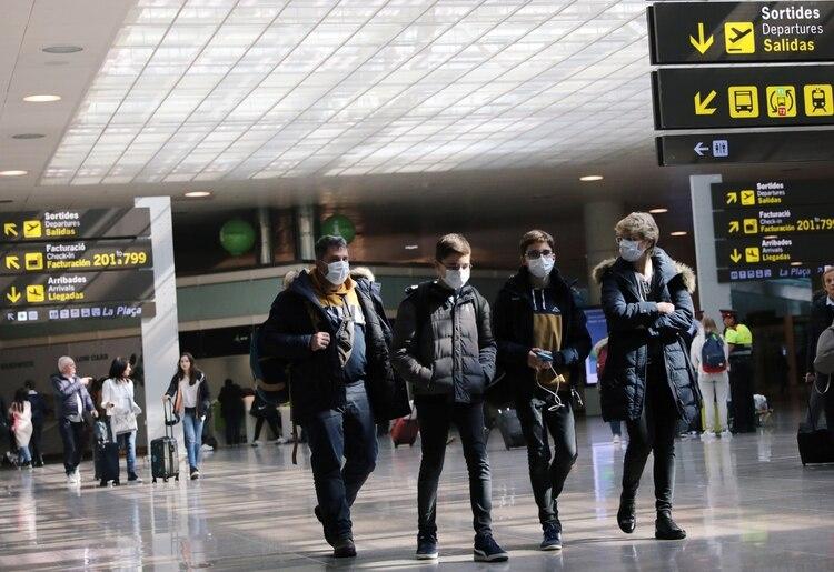 Turistas de diferentes aeropuertos del mundo portaron barbijos a la hora de trasladarse (REUTERS/Nacho Doce)