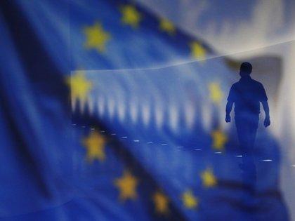 Berlin, Allemagne - 18 décembre: un homme marche dans le couloir du Bundestag allemand alors qu'un drapeau de l'UE se reflète sur un panneau de verre le 18 décembre 2020 à Berlin, en Allemagne.  L'Union européenne et le Royaume-Uni peinent à trouver un accord alors que les négociations sur le Brexit se poursuivent.  (Photo par Michele Tantussi / Getty Images) Photographe: Michele Tantussi / Getty Images Europe