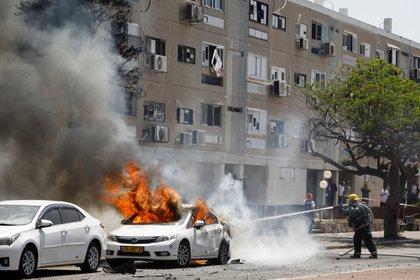 Bomberos israelíes apagan el incendio en un auto alcanzado por un cohete palestino en Ashkelon (REUTERS/Nir Elias)