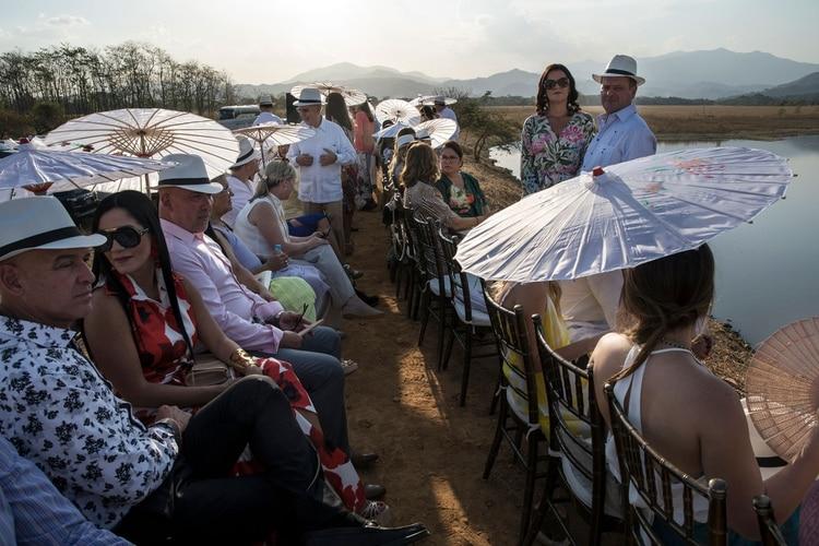 Las mujeres utilizaron vestidos largos y sombrillas de colores y abanicos plegables para mantenerse frescos bajo el sol; los hombres siguieron el atuendo recomendado de camisas blancas, tirantes y pantalones beige, y se pusieron sombreros de Panamá proporcionados por los organizadores