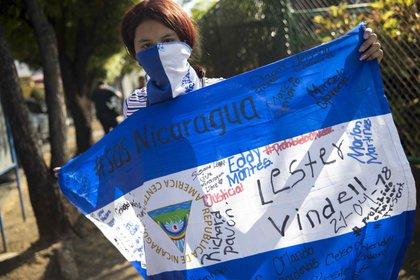 Una joven con la cara tapada y una bandera de Nicaragua participa de una protesta contra el Gobierno del presidente Daniel Ortega en Managua. EFE/Jorge Torres/Archivo