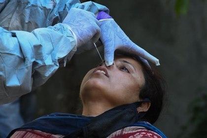Un médico toma una muestra de coronavirus con la técnica de PCR (Photo by NARINDER NANU / AFP)