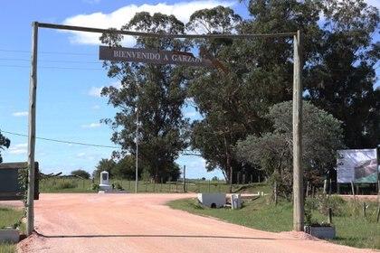 El ingreso al pueblo a través de un camino de ripio y carteles que anuncian mejoras en la infraestructura