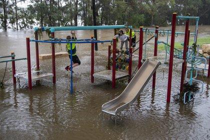 Gente jugando en una zona de juegos inundada en la orilla del río Nepean, en Jamisontown, a las afueras occidentales de Sydney, el lunes 22 de marzo de 2021. (AP Foto/Mark Baker)