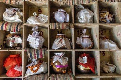 FOTO DE ARCHIVO: Urnas que contienen cenizas de personas que incluyen a fallecidos por la enfermedad del coronavirus (COVID-19) esperan ser sumergidas debido al confinamiento, en un crematorio en Nueva Delhi, India. 6 de mayo de 2021. REUTERS/Danish Siddiqui/