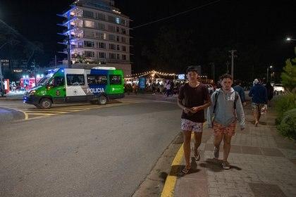 Dos jóvenes sin barbijo caminan por la esquina de Libertador y Bunge, pleno centro de Pinamar