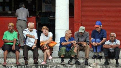 Un grupo de ancianos conversa en la puerta de una bodega en La Habana. (EFE)