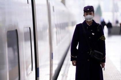 Una mujer del personal del metro de Shanghai en China, usa una mascarilla para protegerse del coronavirus