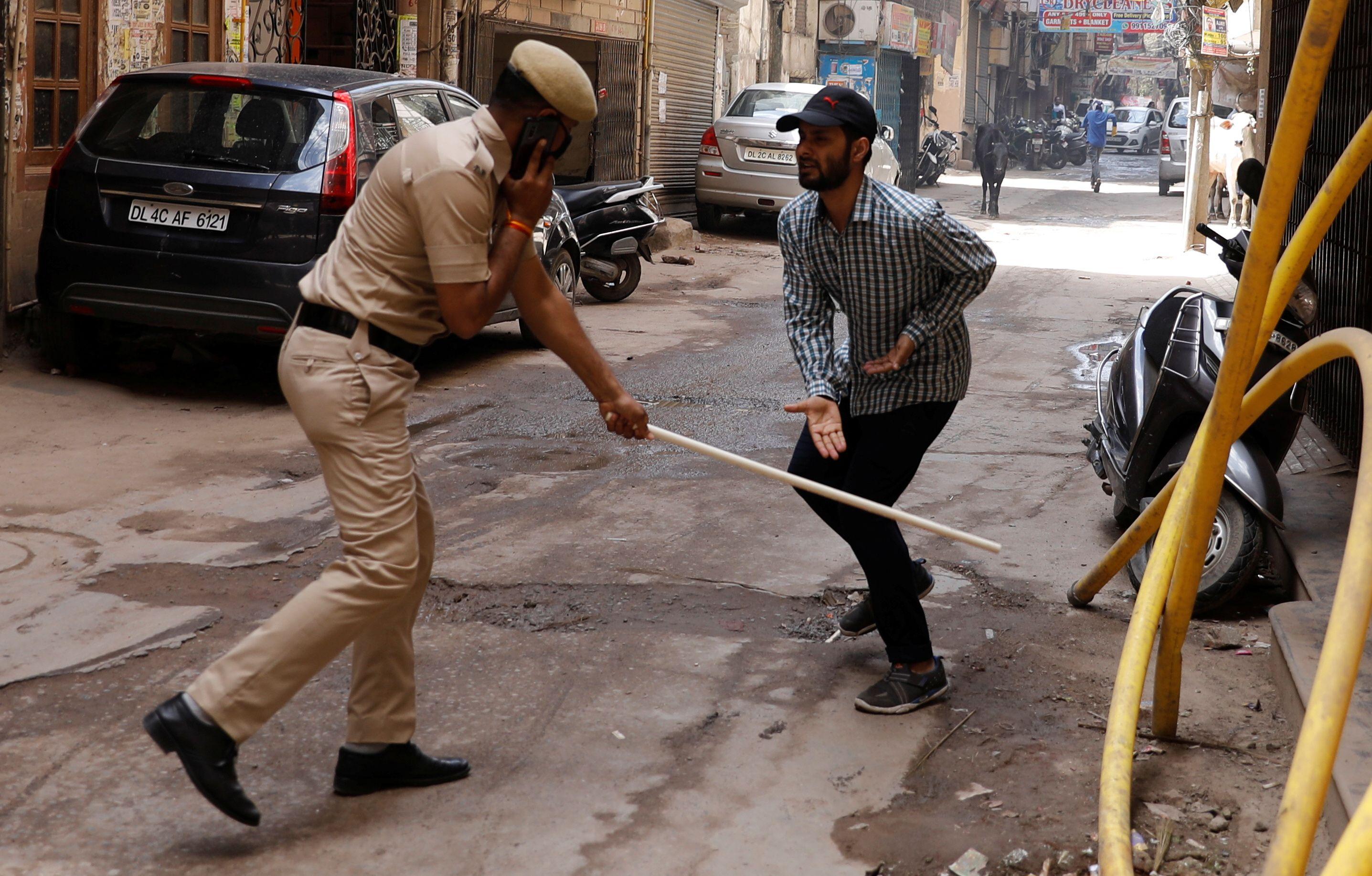 Un policía indio golpea a un transeúnte por quebrar la cuarentena en Nueva Delhi (Reuters)
