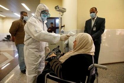 Los médicos chequean la temperatura de la paciente para determinar si puede ser transmisora del nuevo virus