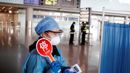 A staff member wears protective gear at the temperature check station of the arrival hall in Beijing Capital Airport as the country is hit by an outbreak of the novel coronavirus, in Beijing, China, March 4, 2020. REUTERS/Thomas Peter