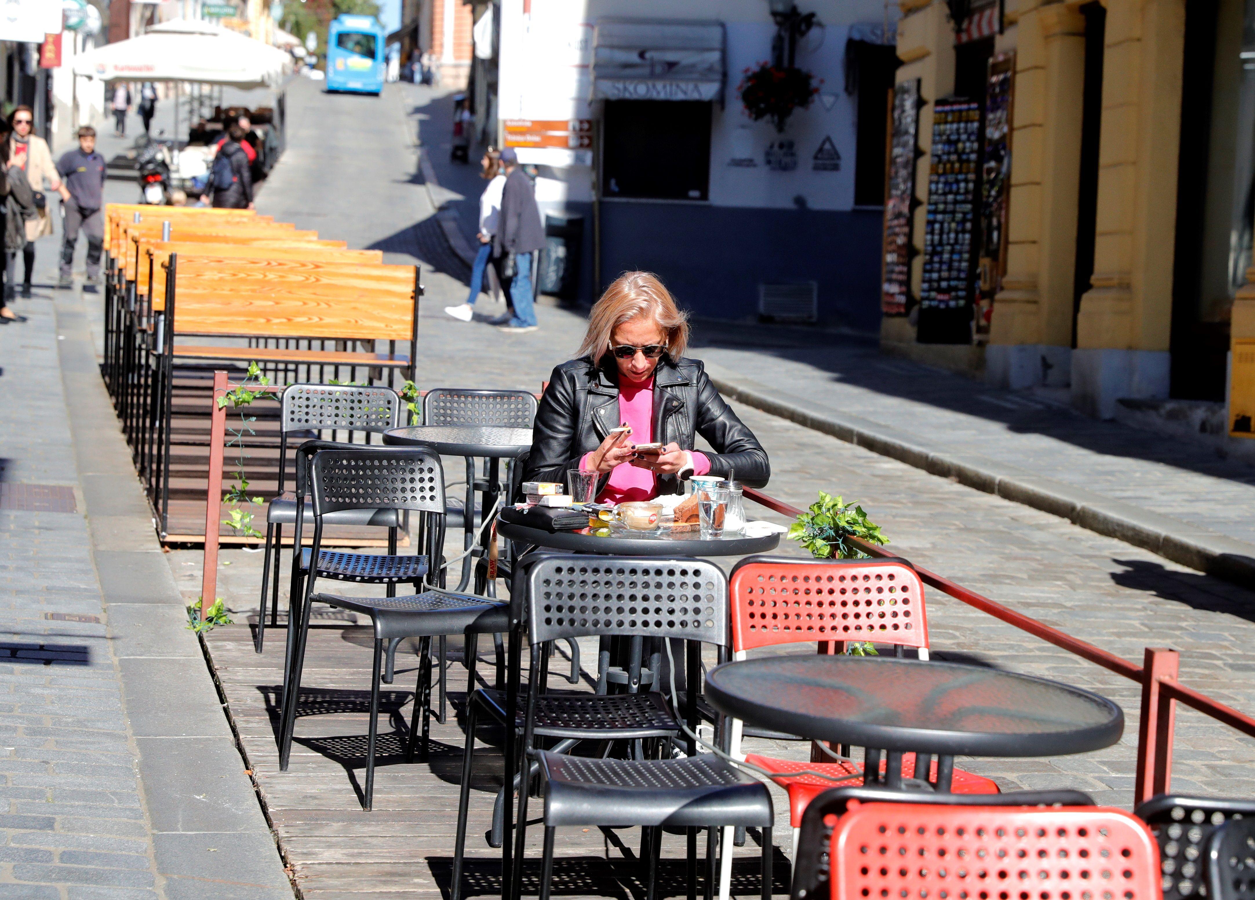 Una mujer sentada en la terraza de un café prácticamente vacía en Zagreb. EFE/EPA/ANTONIO BAT/Archivo