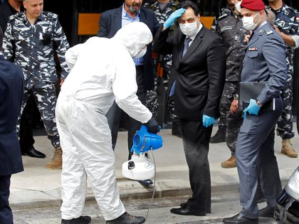 FILE PHOTO: Lebanese Prime Minister Hassan Diab is sprayed with disinfectant as he arrives to attend a legislative session in a theatre hall to allow social distancing amid spread of the coronavirus disease (COVID-19), in the UNESCO Palace building in Beirut, Lebanon April 21, 2020. REUTERS/Mohamed Azakir/File Photo