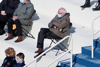 El senador estadounidense Bernie Sanders se sienta socialmente distanciado mientras asiste a la inauguración presidencial de Joe Biden en el frente occidental del Capitolio de los Estados Unidos en Washington.  Caroline Brehman/Pool via REUTERS