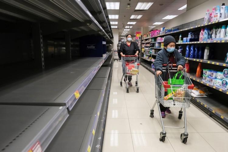 Compradores con mascarillas en un supermercado desabastecido en Hong Kong (REUTERS/Tyrone Siu)
