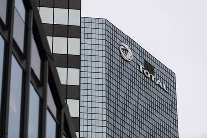 A logo on the Total SE headquarters in the La Defense business district in Paris, France, on Thursday, Jan. 21, 2021. The shift of jobs and assets to Paris after Brexit will accelerate this year, providing Europe with an opportunity to strengthen its own financial infrastructure, according to Bank of France Governor Francois Villeroy de Galhau. Photographer: Benjamin Girette/Bloomberg