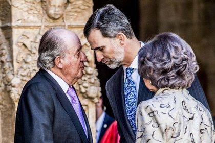 El rey emérito junto con su hijo, Felipe y su madre Sofía, de espaldas, en Palma de Mallorca, en una de las últimas imágenes de ambos juntos (Shutterstock)