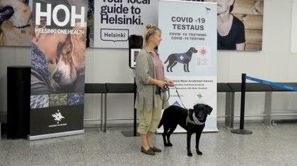 La entrenadora Susanna Paavilainen con el perro rastreador Miina, siendo entrenada para detectar el coronavirus de las muestras de los pasajeros que llegan, en el aeropuerto de Helsinki en Vantaa, Finlandia, el 22 de septiembre de 2020 (REUTERS/Attila Cser)