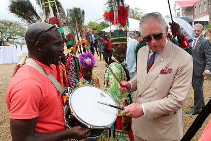 El Príncipe Carlos prueba un tambor mientras asiste a una recepción en la Casa de Gobierno en Nevis, en San Cristóbal y Nieves, el 21 de marzo de 2019 (Chris Jackson/Pool vía REUTERS)