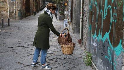 Una mujer coloca comida en una canasta solidaria, disponible para las personas de menos recursos (Carlo Hermann / AFP)