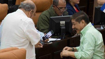 El diputado Edwin Castro (de espaldas) cuando se burlaba de los diputados opositores que llegaron con mascarillas al parlamento. (Foto cortesía La Prensa)