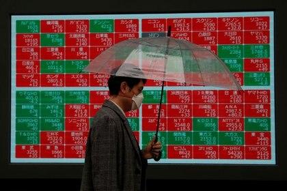 FOTO DE ARCHIVO. Un peatón con una mascarilla, debido al brote del coronavirus, pasa frente a un tablero de cotización de acciones frente a una correduría en Tokio, Japón. 2 de marzo de 2020. REUTERS/Issei Kato